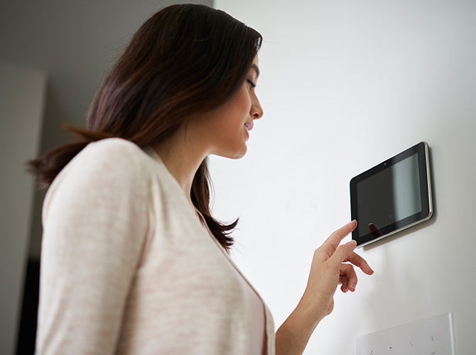 Woman adjusting smart thermostat in her home
